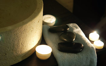 Massage hot stones lit by candle light